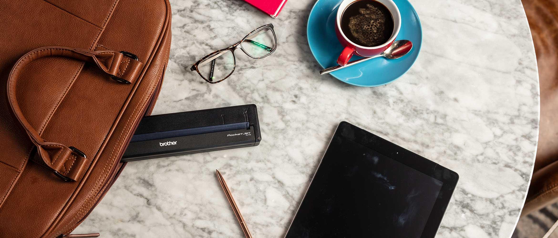 Barna táska, Brother PJ mobil nyomtató, ceruza, tablet, kávéscsésze kávéval, jegyzettömb