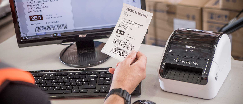 Brother QL-1100 asztali címkenyomtató, a használója egy kinyomtatott címkét tart a kezében