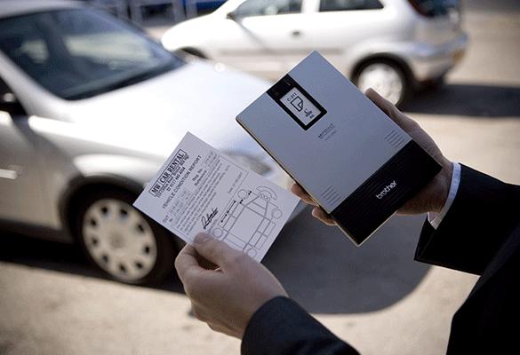 Egy ember kezében tartja az MW nyomtatót, amely A6 méretű anyagot  nyomtatott autókölcsön-űrlappal
