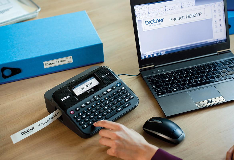 P-touch címkenyomtató irodai íróasztalon, laptophoz csatlakoztatva, címkenyomás közben