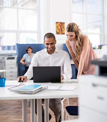 Hölgy áll az asztal mellettegy öltönyös férfi mellett, a háttérben nyomtató