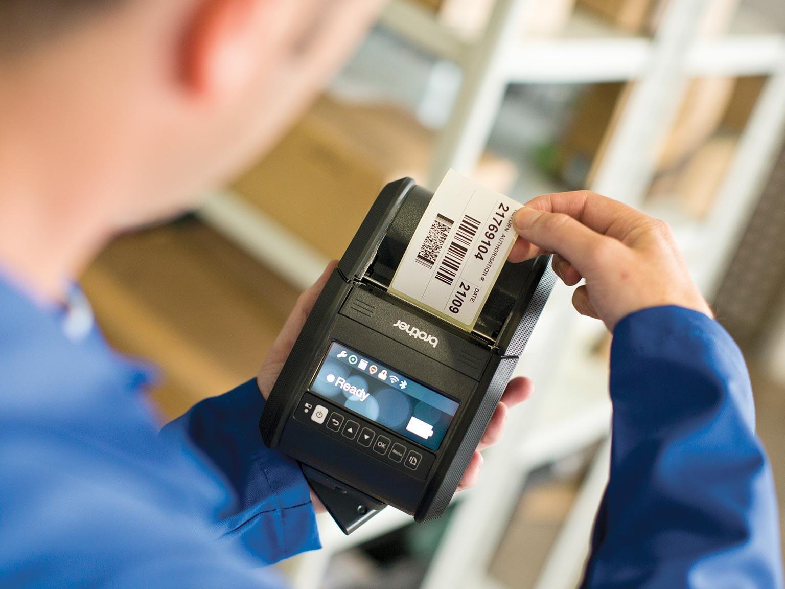 Egy raktári munkás RJ sorozatú címkenyomtatót tart a kezében a címke nyomtatása közben