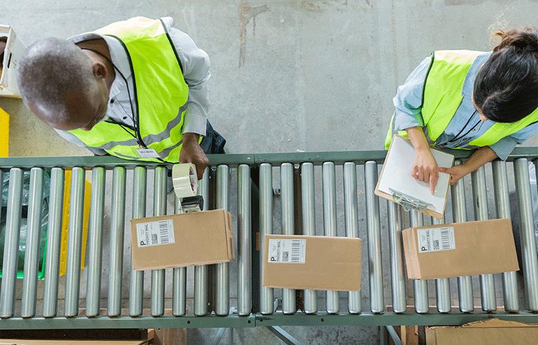 Egy ember címkefelrakóval áll a dobozok felett a futószalagnál, mellette egy hölgy, mindketten jólláthatósági mellényben vannak