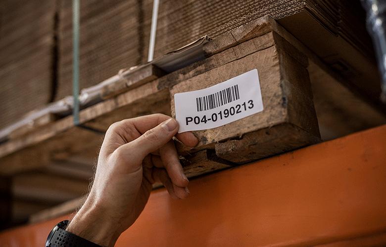 A vonalkódcímkét egy munkatárs a kezével a raklapra ragasztja