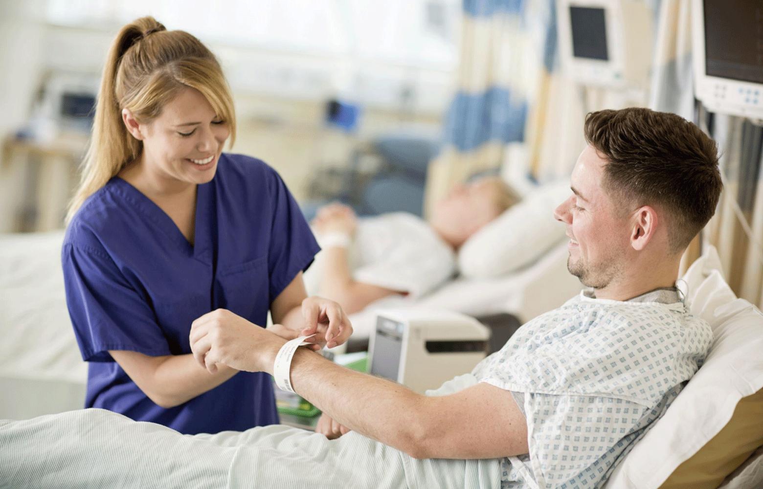 A nővér csuklópántot készít TD nyomtatóval egy férfi betegnek