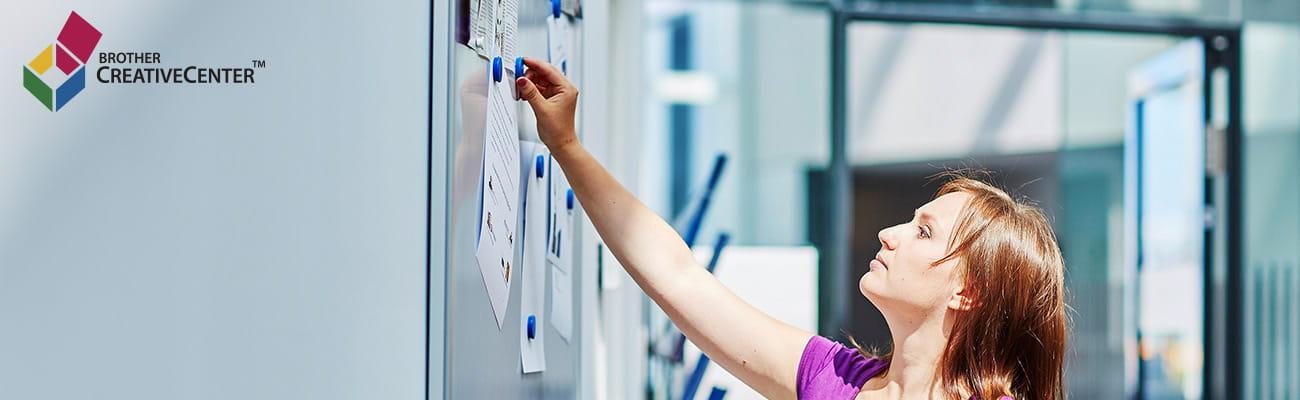 nő rögzít jegyzeteket a falhoz egy irodában