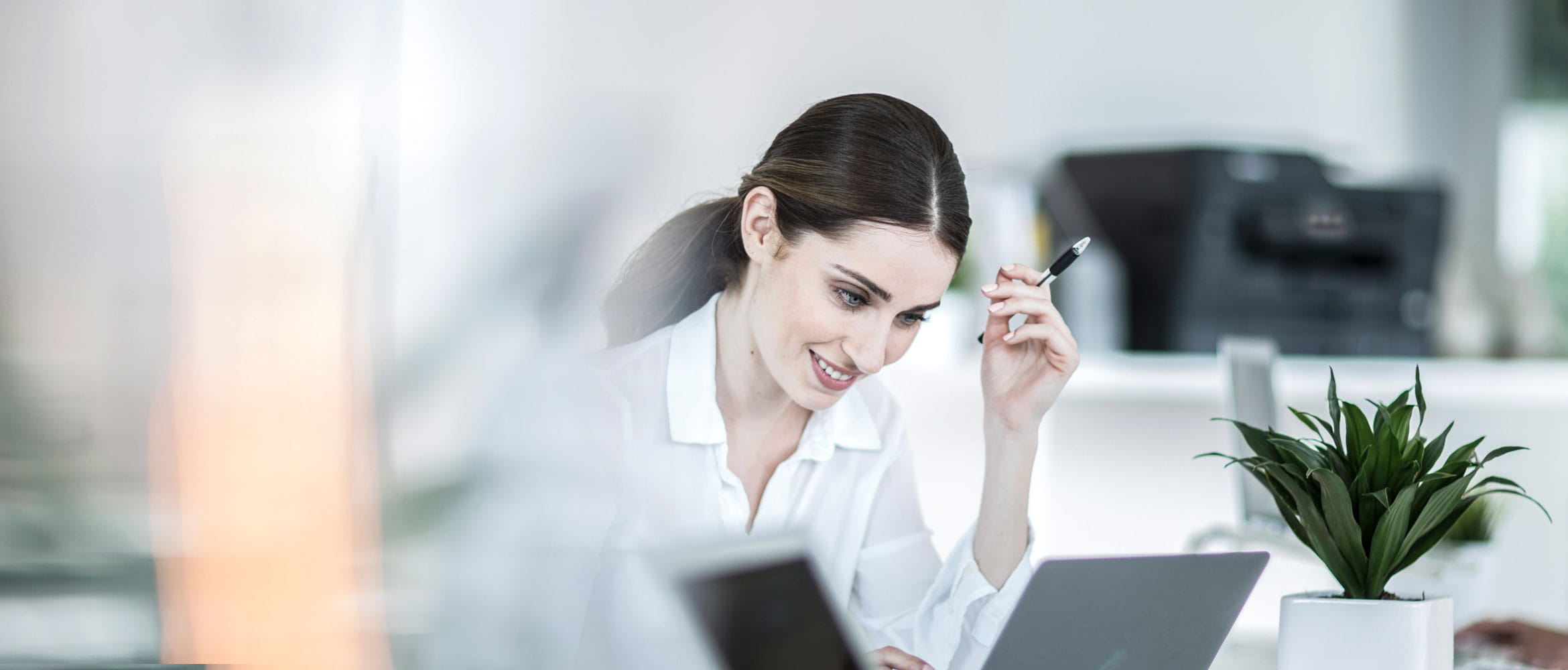 Woman sitting at her desk using her laptop with pen in her hand