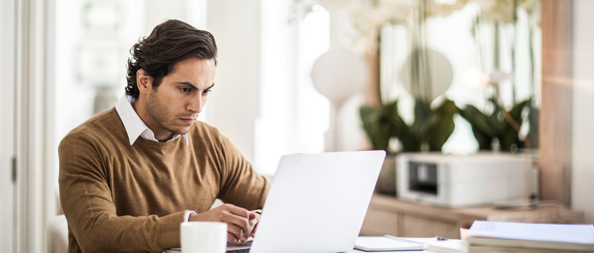 Man looking at laptop in home setting