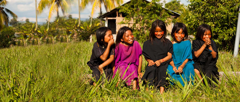 Five children laugh in sunny field