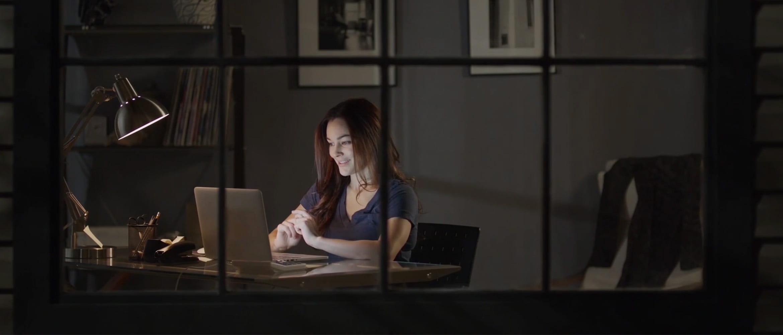 Nő ül egy asztalnál- este-laptoppal