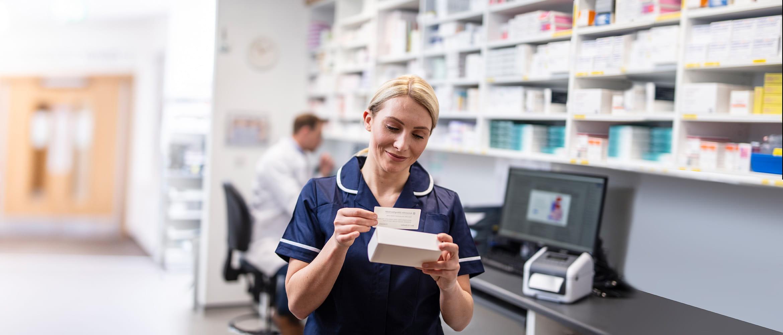 Egészségügyi dolgozó egy gyógyszert címkéz