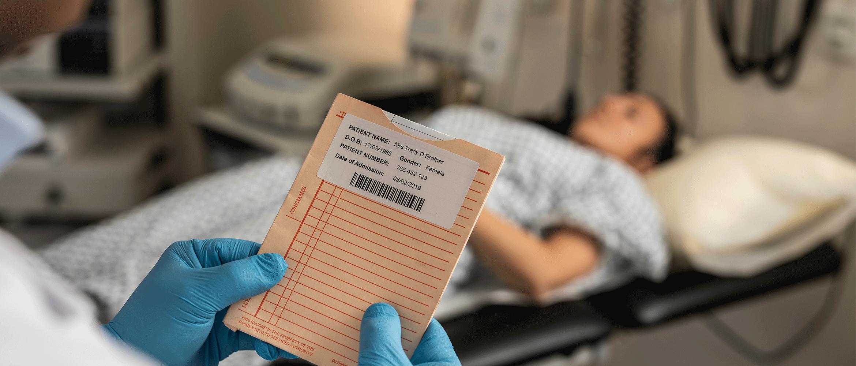 Hölgy a kórházi ágyon, az orvos a kórlapot nézi