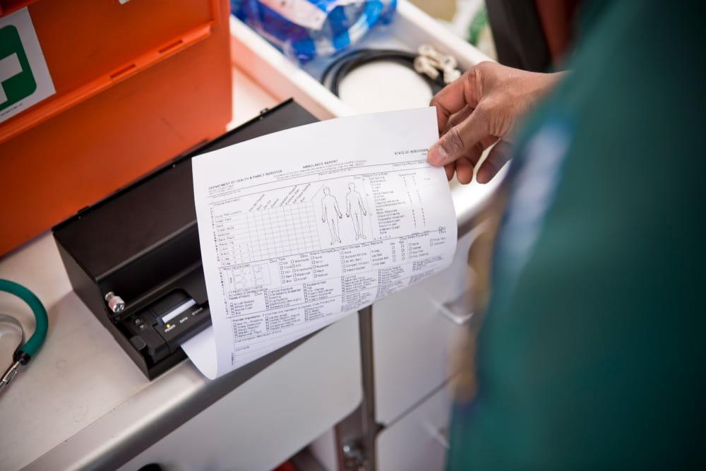 férfi A4-es dookumentumot nyomtat mentőautóban