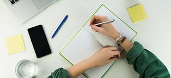jegyzetelés egy asztalon, mobiltelefon látható