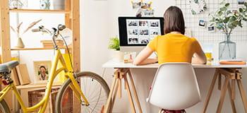nő ül az asztalnál otthoni irodájában és egy sárga bicikli is látható