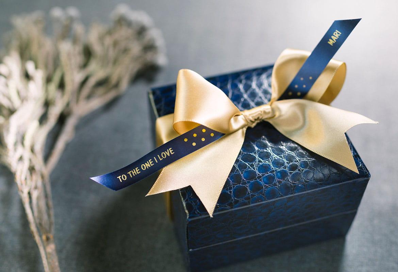 Ajándékdoboz sárga szalaggal díszítve, és Brother kék szatén szalagon arannyal nyomtatott üzenettel