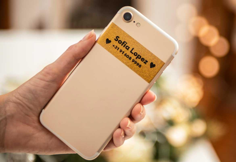 Prémium arany csillogó címkén fekete felirat okostelefonon, a tulajdonos nevével és elérhetőségével
