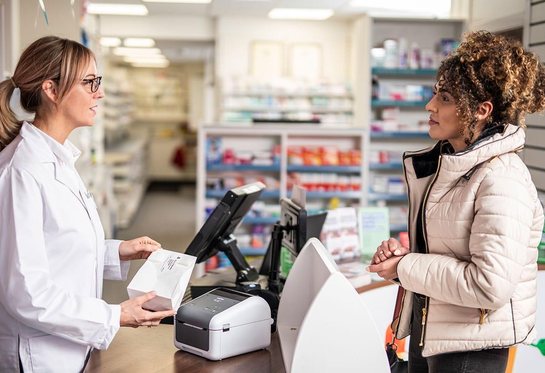 Női gyógyszerész szemüvegben a kiszolgáló pultnál egy göndör hajú, kabátot viselő női pácienssel