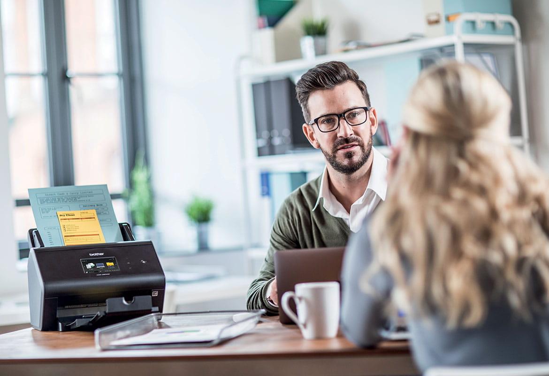 Szemüveget és pulóvert viselő férfi ül az íróasztalnál Brother szkennerrel, egy hosszú hajú női ügyfél ül az asztal másik oldalán