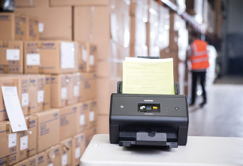 Brother ADS-3600W szkennerben szállítói jegyzetek a raktárban, raktári munkás narancssárga mellényt visel a háttérben, dobozok, asztal a képen