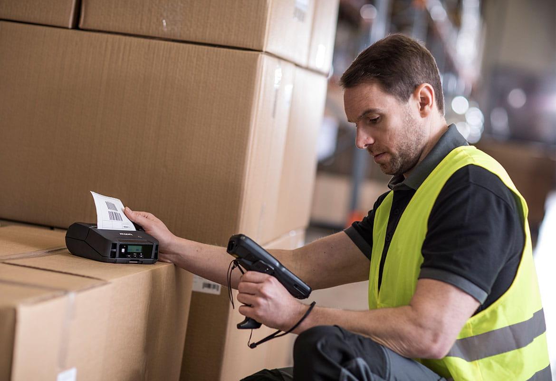 Jólláthatósági mellényt viselő férfi bloknyomtatóval dolgozik egy doboz tetejére téve egy raktárban