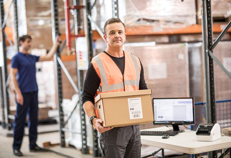Barna, rövid hajú férfi jólláthatósági mellényben barna dobozt tart a kezében, monitor, billentyűzet,egér a képen