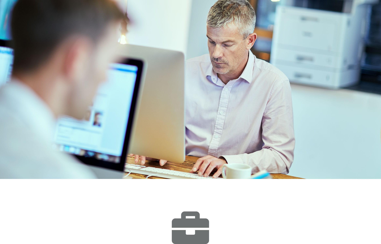Két ember ül az asztalnál, számítógépekkel dolgozva a háttérben lézernyomtató