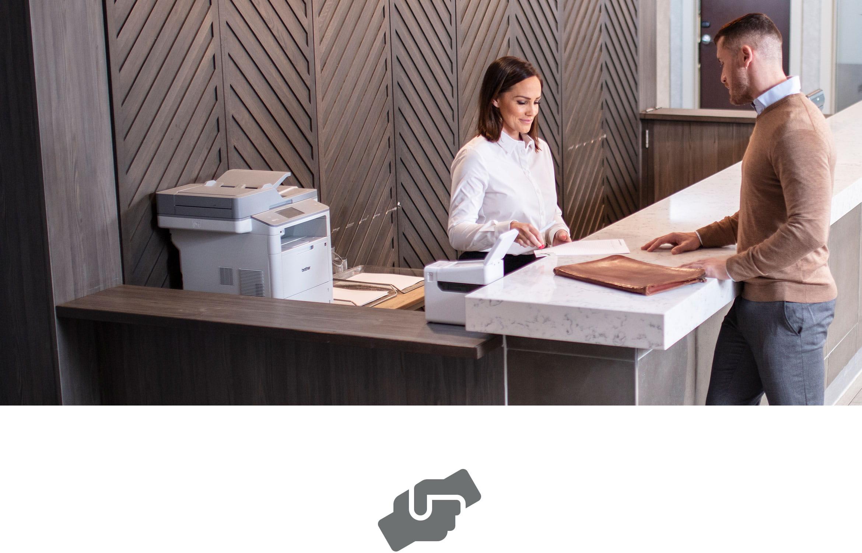 Férfi ügyfél az ügyfélszolgálattól segítséget kap a pultnál, lézer- és címkenyomtató vannak a pulton