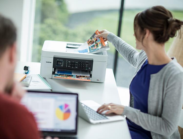 Az otthoni irodában egy nő a nyomtató mellett áll