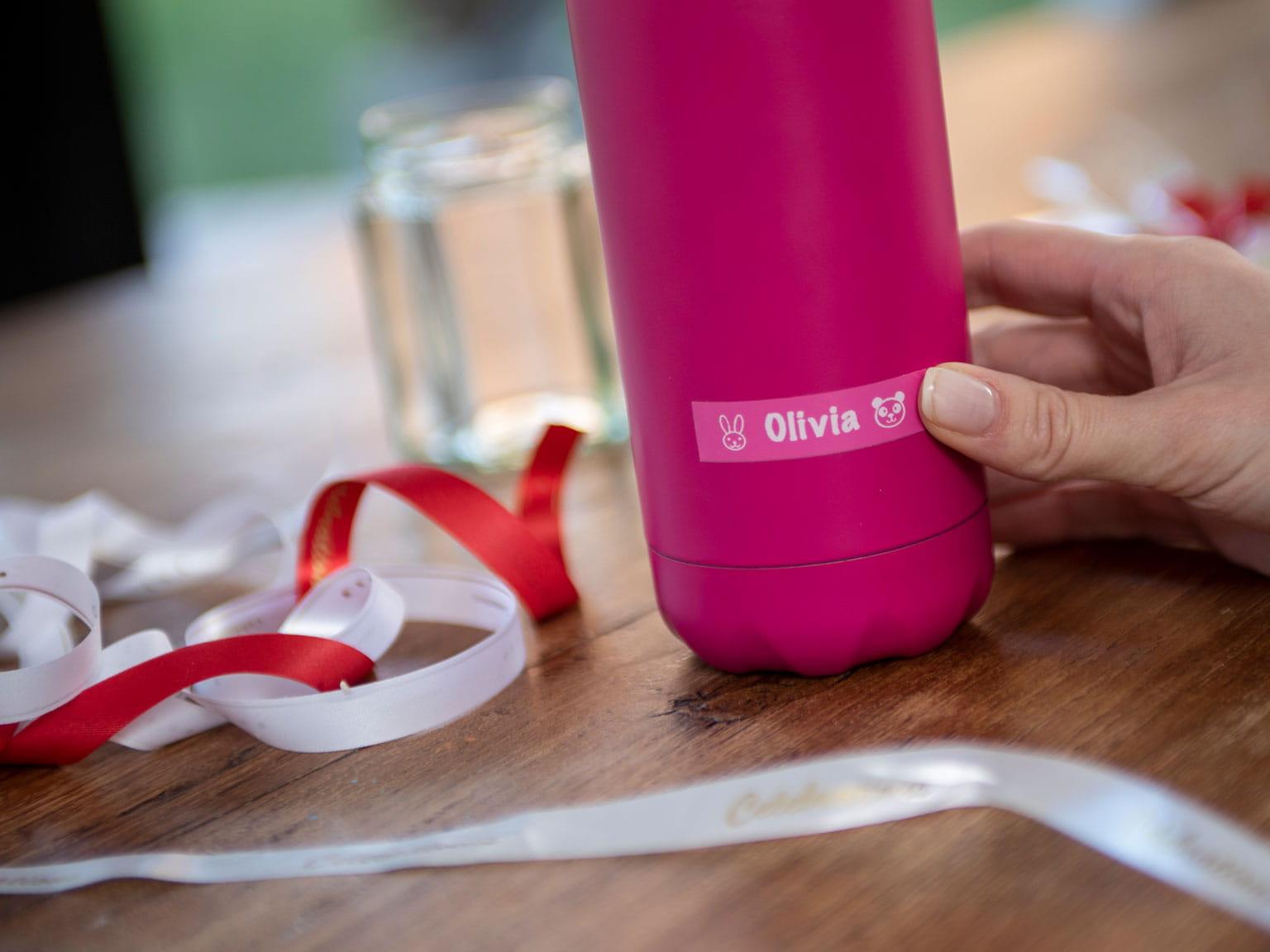 Brother rózsaszín címke rózsaszín vizes palackon, fehér és piros selyemszalaggal körülötte