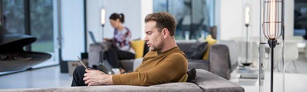 ember ült egy kanapén dolgozik egy tabletta
