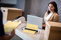 Barna hajú hölgy a recepción laptop segítségével Brother DSmobile DS740D hordozható dokumentum szkenner az asztalon, dobozokkal, szállítólevél