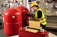A mérnök sárga munkavédelmi sisakot és jólláthatósági mellényt visel, a Brother DSmobile DS-940DW hordozható dokumentumolvasóval a gépházban